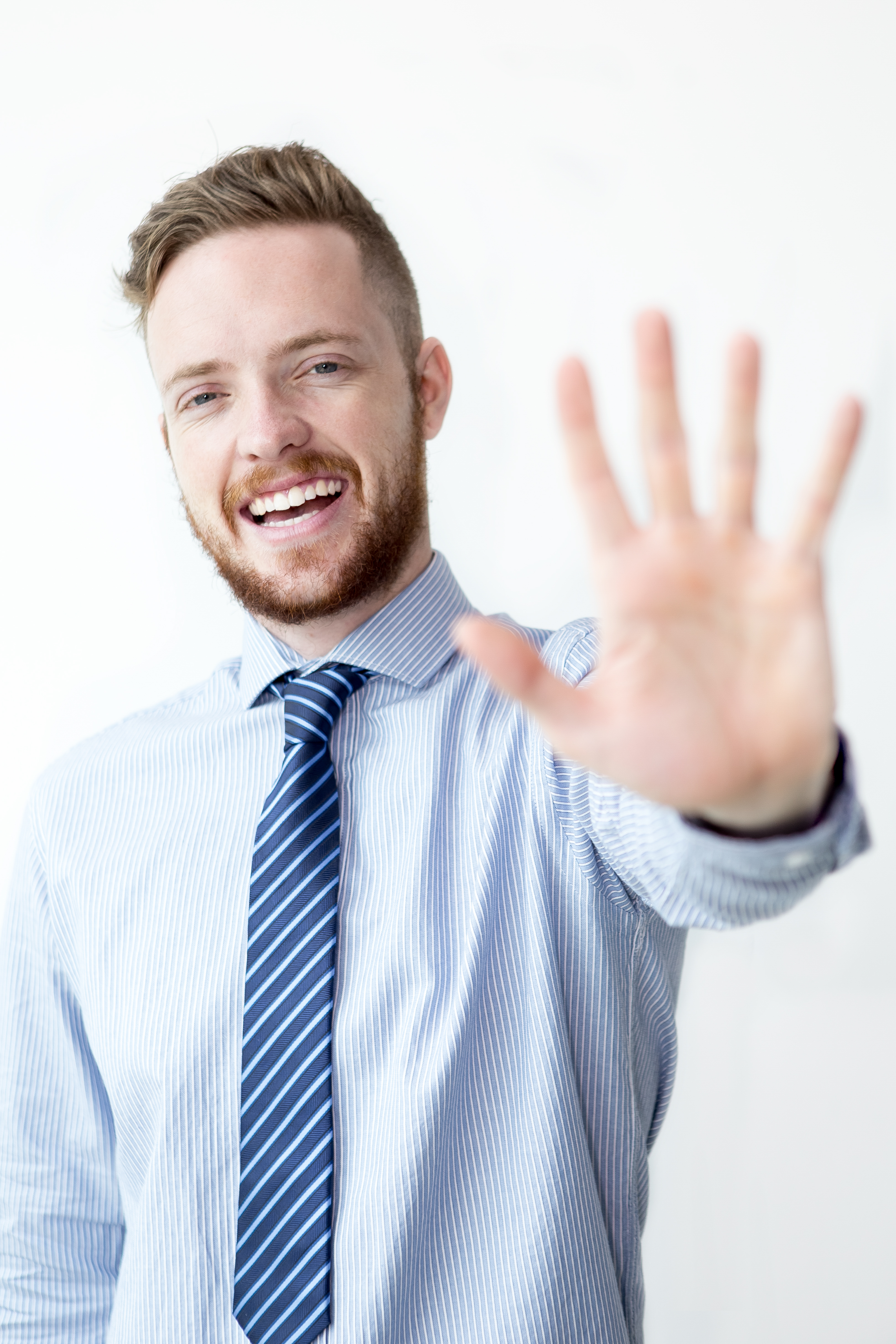 Closeup portrait of smiling young business man looking at camera and showing open palm or stop gesture. Isolated front view on white background.